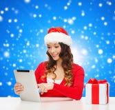 Femme de sourire dans le chapeau de Santa avec le PC de cadeau et de comprimé Photographie stock