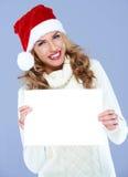 Femme de sourire dans le chapeau de Santa retenant le panneau blanc Photos stock