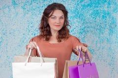 Femme de sourire dans le chemisier orange tenant le papier coloré d'achats Images libres de droits