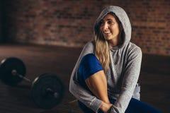 Femme de sourire dans le hoodie détendant au studio de forme physique photo libre de droits