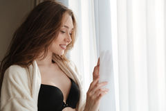 Femme de sourire dans le peignoir et la lingerie se tenant près de la fenêtre images stock
