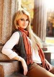 Femme de sourire dans le rétro style sur une rue de ville en automne Images stock