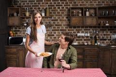 femme de sourire dans le tablier servant le dîner fait maison pour l'ami Photo stock