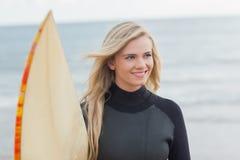 Femme de sourire dans le vêtement isothermique avec la planche de surf à la plage Photographie stock