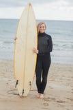 Femme de sourire dans le vêtement isothermique tenant la planche de surf à la plage Images stock