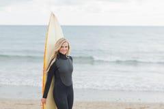 Femme de sourire dans le vêtement isothermique tenant la planche de surf à la plage Photos stock