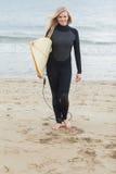 Femme de sourire dans le vêtement isothermique tenant la planche de surf à la plage Photographie stock libre de droits