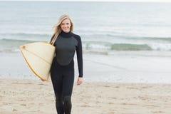 Femme de sourire dans le vêtement isothermique tenant la planche de surf à la plage Photo stock