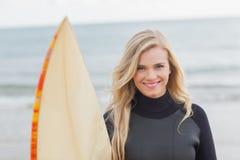 Femme de sourire dans le vêtement isothermique tenant la planche de surf à la plage Photographie stock