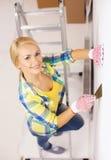 Femme de sourire dans les gants faisant des rénovations à la maison Photo libre de droits