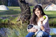 Femme de sourire de brune étreignant son chien blanc avec la pomme dans la main Image libre de droits