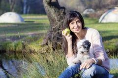 Femme de sourire de brune étreignant son chien blanc avec la pomme dans la main Photos stock