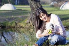 Femme de sourire de brune étreignant son chien blanc avec la pomme dans la main Image stock