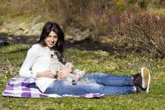 Femme de sourire de brune étreignant son chien blanc extérieur Photo stock