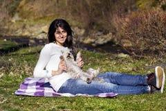 Femme de sourire de brune étreignant son chien blanc extérieur Image stock