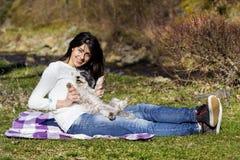 Femme de sourire de brune étreignant son chien blanc extérieur Images stock