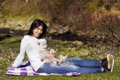 Femme de sourire de brune étreignant son chien blanc extérieur Image libre de droits