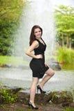 Femme de sourire de brunette restant à l'étang Photo stock