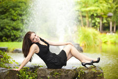 Femme de sourire de brunette s'asseyant à l'étang Images libres de droits