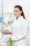 Femme de sourire de chimiste de pharmacie dans la pharmacie Image stock