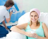 Femme de sourire de détente s'asseyant sur le sofa Images libres de droits