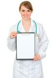 Femme de sourire de docteur retenant la planchette blanc Photos stock