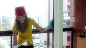 Femme de sourire de fille pulvérisant la fenêtre chimique et lavante clips vidéos
