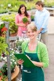 Femme de sourire de fleuriste aux stocks de jardinerie photo libre de droits