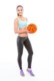 Femme de sourire de forme physique tenant la boule de basket-ball image libre de droits