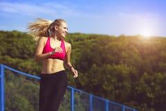 Femme de sourire de sport courant en parc Photographie stock
