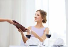 Femme de sourire donnant le menu au serveur au restaurant Image stock