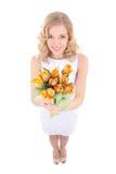 Femme de sourire drôle avec les tulipes oranges d'isolement sur le blanc Photos stock