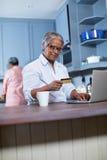 Femme de sourire employant la carte de crédit tout en faisant des achats en ligne Image stock