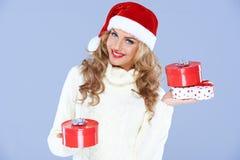Femme de sourire en cadeaux de transport d'un chapeau de Santa Photographie stock