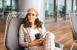 Femme de sourire en caf? d'a?roport avec la tasse de caf? images stock