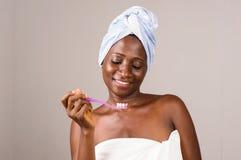 Femme de sourire en serviette avec les dents saines tenant la brosse à dents photo libre de droits