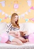 Femme de sourire enceinte s'asseyant sur un sofa Photographie stock