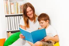 Femme de sourire enseignant son garçon d'enfant à lire Photo stock