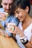 Femme de sourire et homme riant avec des tasses de cappuccino Image libre de droits