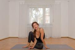 Femme de sourire exerçant le yoga sur le tapis à la maison image stock
