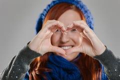 Femme de sourire faisant la forme de coeur avec des mains Image stock