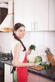 Femme de sourire faisant la nourriture saine dans la cuisine images stock