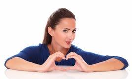 Femme de sourire faisant un signe d'amour Photographie stock libre de droits