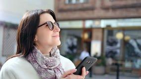 Femme de sourire fascinante dans des lunettes de soleil introduisant le message utilisant le smartphone sur la rue moderne de vil banque de vidéos