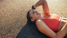 Femme de sourire de forme physique faisant la pause de la séance d'entraînement se trouvant sur la terre Athlète gai de femme se  photographie stock