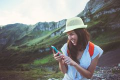 Femme de sourire gaie avec le téléphone portable Chemin touristique de beaux prés de montagne Textoter avec des amis dans le rése Photographie stock libre de droits