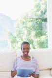 Femme de sourire heureuse à l'aide du comprimé numérique sur le divan Photos stock