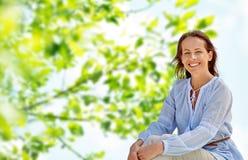 Femme de sourire heureuse au-dessus de fond naturel vert image libre de droits