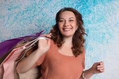 Femme de sourire heureuse aux achats avec les sacs en papier colorés Image stock