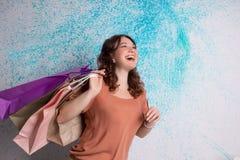 Femme de sourire heureuse aux achats avec les sacs en papier colorés Photographie stock